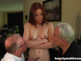 Young redhead floozy drops on her knees to please two old dicks